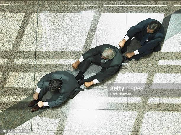 three businessmen lined up in crew rowing position, overhead view - hans neleman ストックフォトと画像