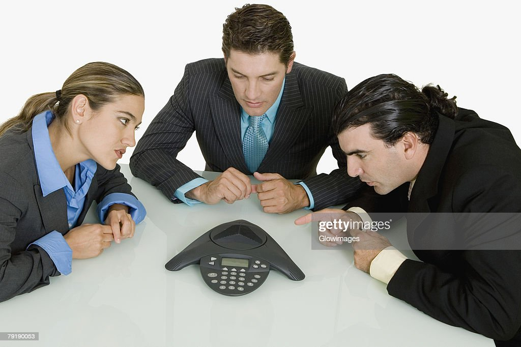 Three businessmen listening to a conference call : Stock Photo