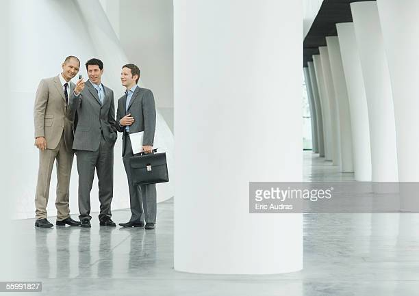 Three businessmen looking at cell phone in lobby