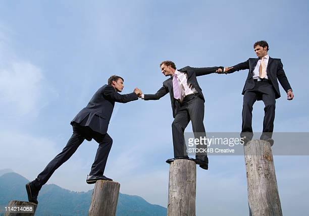 Three businessmen on logs, low angle view