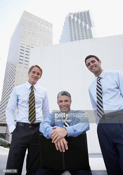 Drei Geschäftsleute im Freien mit Stuhl