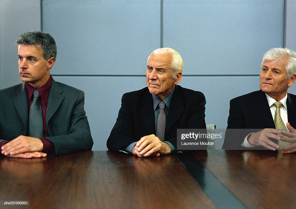 Three businessmen sitting at conference table with hands on table, portrait : Stockfoto