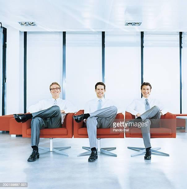 three businessmen sitting in armchairs, smiling, portrait - drei personen stock-fotos und bilder
