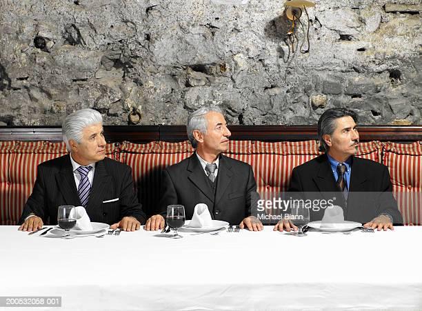 three businessmen sitting in restaurant looking to side - repetitie stockfoto's en -beelden