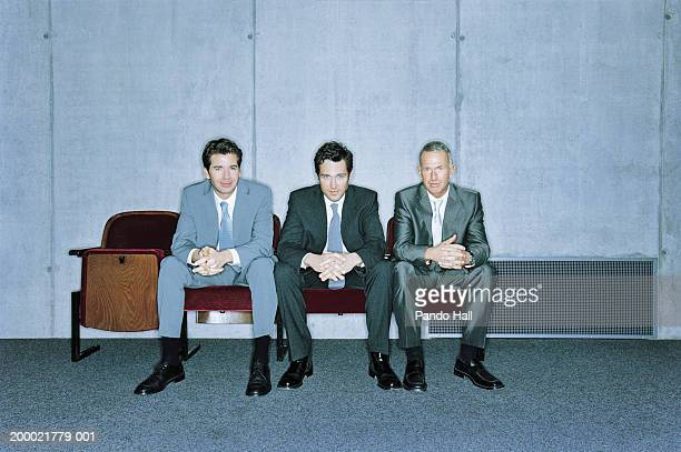 three businessmen sitting in row of chairs, portrait - grey suit stock pictures, royalty-free photos & images