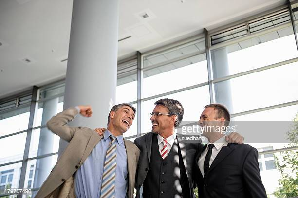 Three businessmen smiling and celebrating