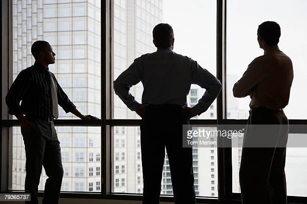 Drei Geschäftsleute stehen in einem Korridor, der von einem großen Fenster