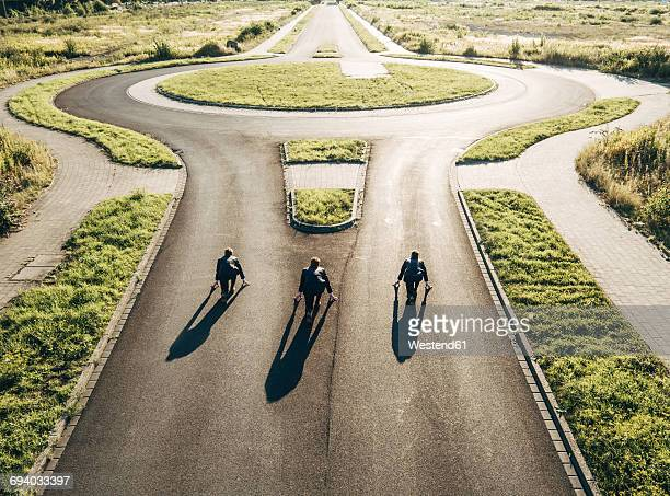 Three businessmen starting race at roundabout