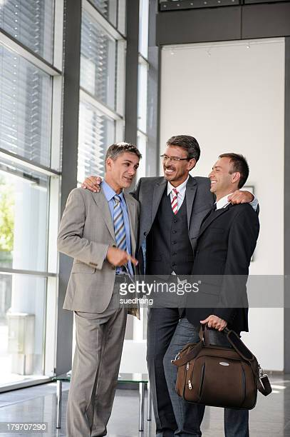 Three businessmen talking and laughing