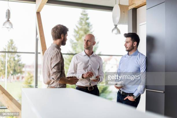 three businessmen talking during coffee break - drei personen stock-fotos und bilder