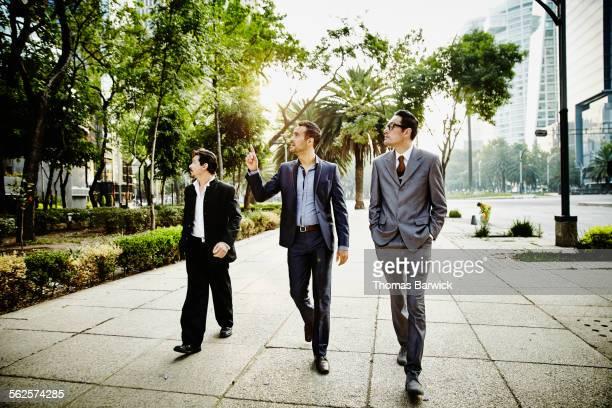 Three businessmen walking on sidewalk in city