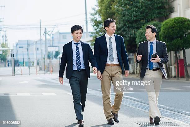 3 つのビジネスマンオフィス外の散歩