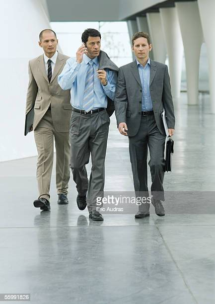 Three businessmen walking through lobby, one using cell phone
