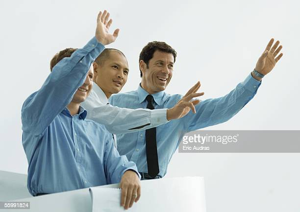 three businessmen waving - waving gesture stock photos and pictures