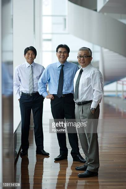 three businessmen who are standing in smile - three people ストックフォトと画像