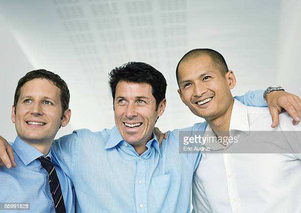 Three businessmen with arms around each others' shoulders