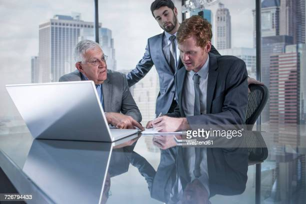 Three businessmen with laptop discussing in office