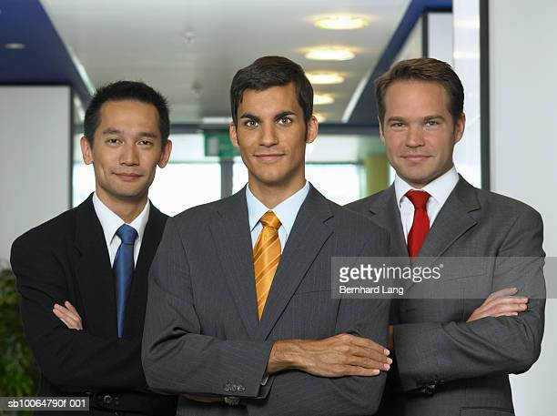 Three businessmen with variously coloured ties, portrait