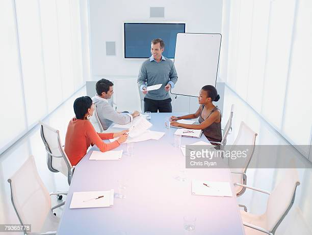 Three businesspeople at a boardroom table with a businessman presenting