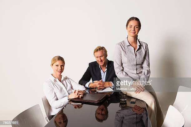 Three businesspeople at a table smiling.