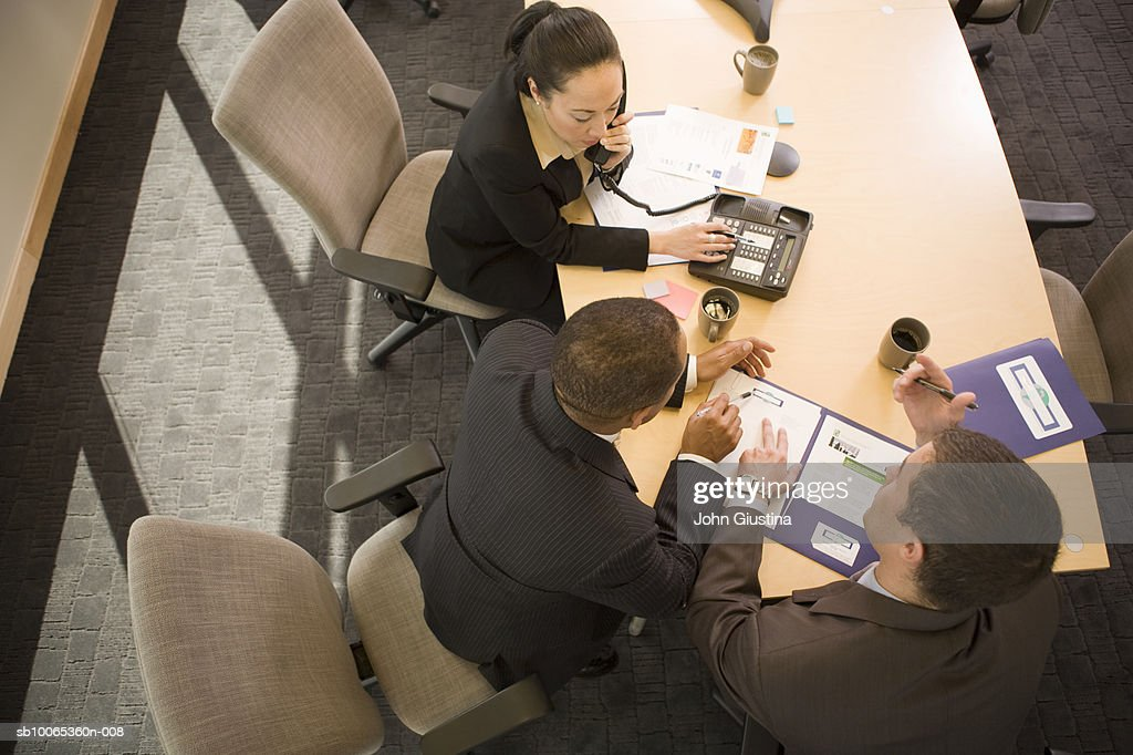 Three businesspeople discussing in conference room, elevated view : Foto stock