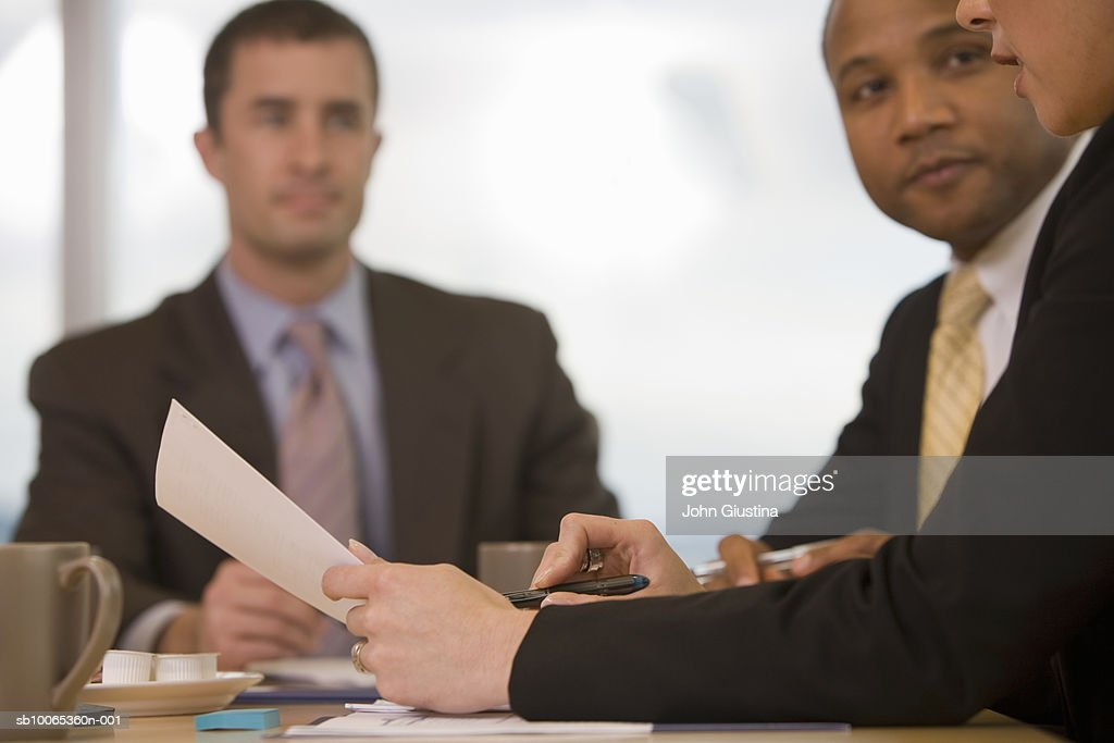 Three businesspeople discussing in conference room (focus on foreground) : Foto stock
