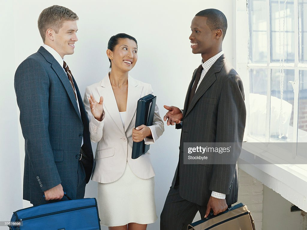 Three businesspeople having discussion, smiling : Stock Photo