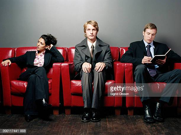 three businesspeople in a row on armchairs, portrait of man in centre - good posture stock pictures, royalty-free photos & images