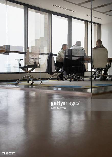three businesspeople in boardroom - distant stock photos and pictures
