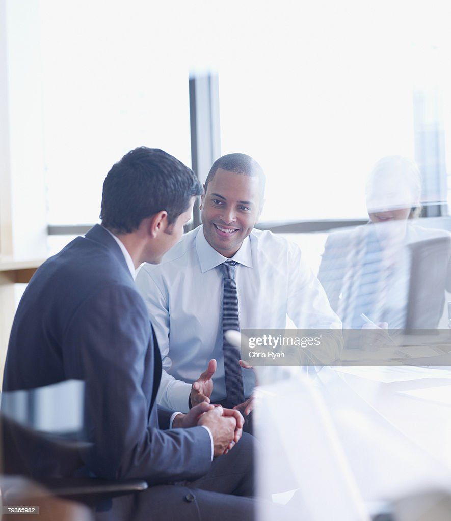 Three businesspeople in boardroom through glass : Stock Photo