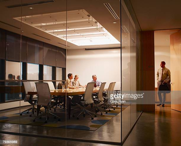 three businesspeople in boardroom watching businessman leave - leaving stock pictures, royalty-free photos & images