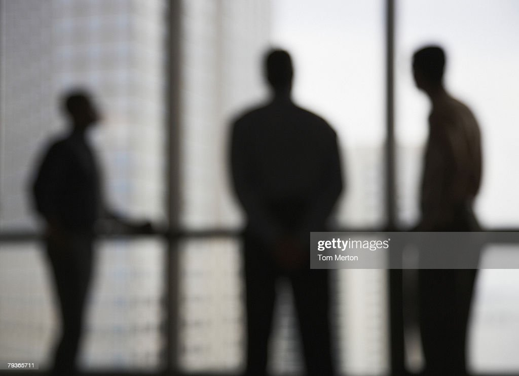 Three businesspeople in corridor by large windows : Stock Photo