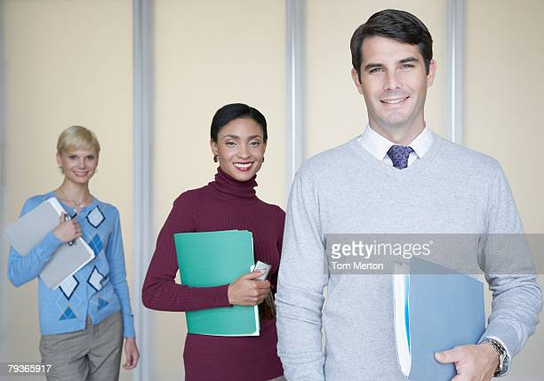 Three businesspeople in office looking at camera