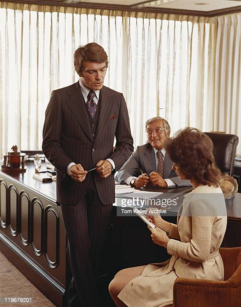 Three businesspeople in office, young woman making notes