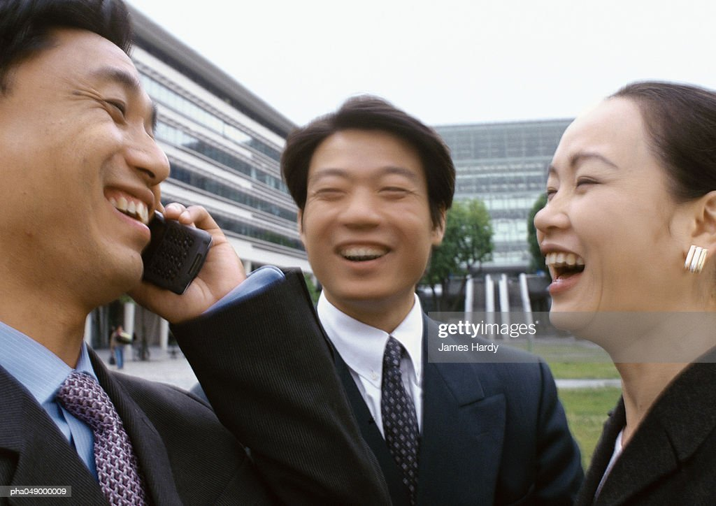 Three businesspeople laughing, one holding cell phone : Stockfoto