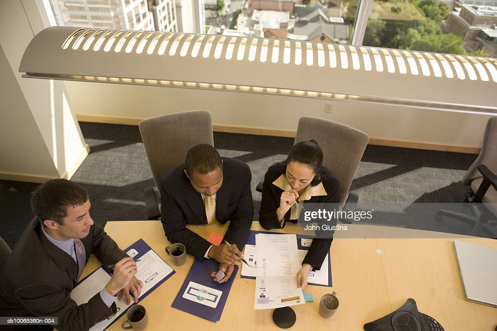 Three businesspeople looking at documents in conference room, elevated view : Foto stock