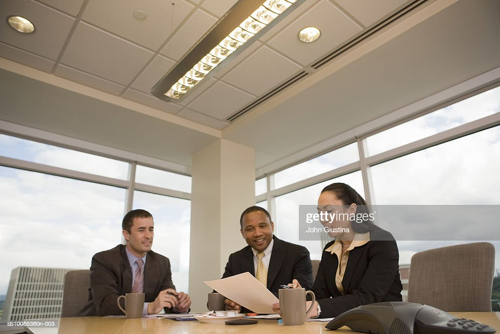 Three businesspeople looking at documents in conference room, smiling : Foto stock