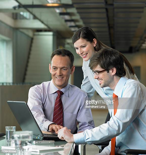 Three businesspeople looking at laptop in office