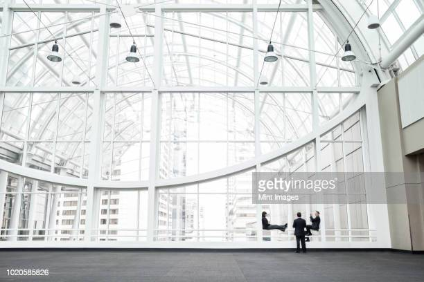 three businesspeople meeting in front of a window in a large convention centre lobby. - building atrium stock pictures, royalty-free photos & images