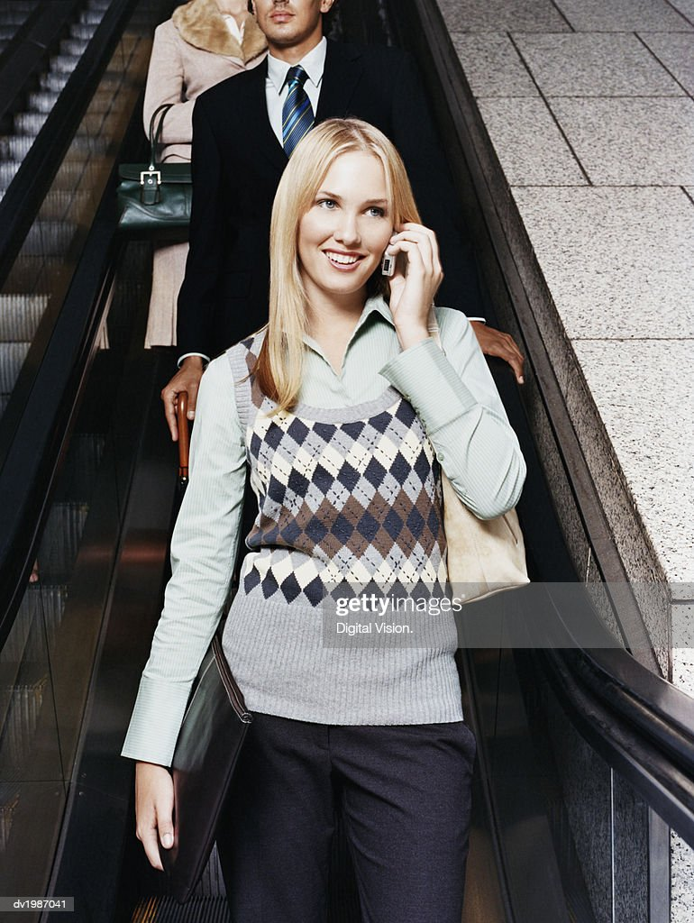 Three Businesspeople on an Elevator, Businesswoman Using a Mobile Phone : Stock Photo