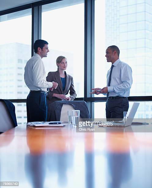 three businesspeople standing in a boardroom - vertical stock pictures, royalty-free photos & images