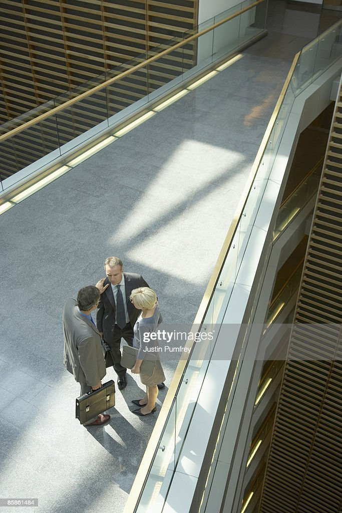 Three businesspeople talking, elevated view : Stock-Foto