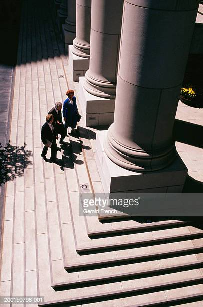 Three businesspeople walking up steps of courthouse, elevated view