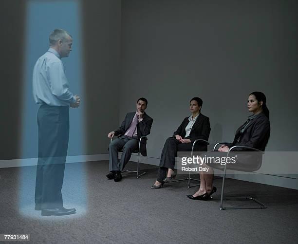 Tres empresarios mirando una holograma de un hombre de negocios