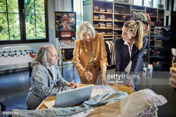 three businesspeople with laptop discussing in fashion store - fashion industry stock pictures, royalty-free photos & images