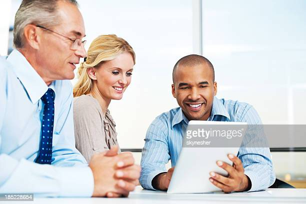 Three businesspeople working on a touchpad.