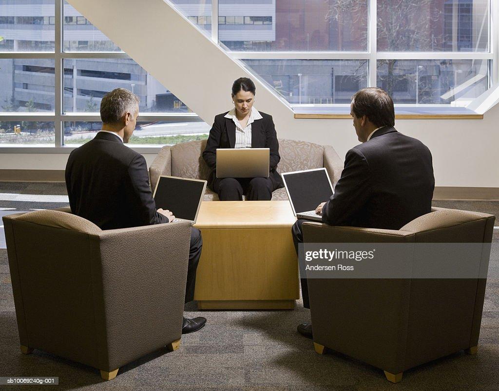 Three businesspeople working on laptop : Stockfoto