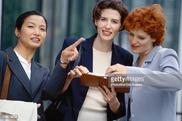 three businesswoman looking at agenda, one pointing out of frame - out of frame stock pictures, royalty-free photos & images