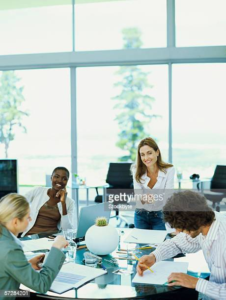 Three businesswomen and a businessman in an  office working at a round table