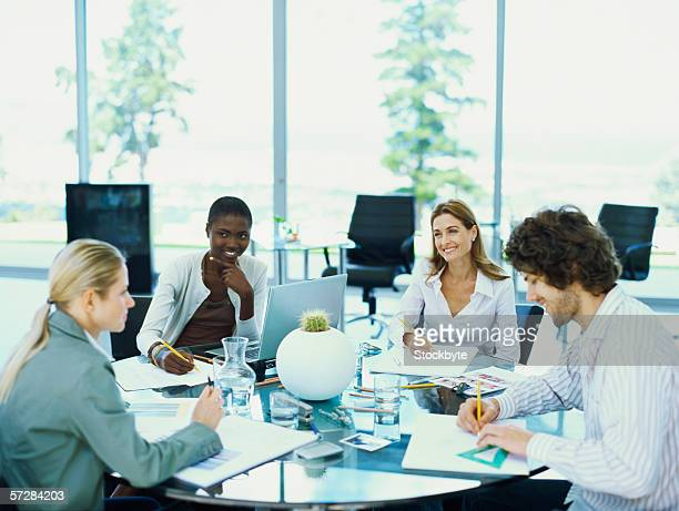 Three businesswomen and a businessman sitting in an office at a round table